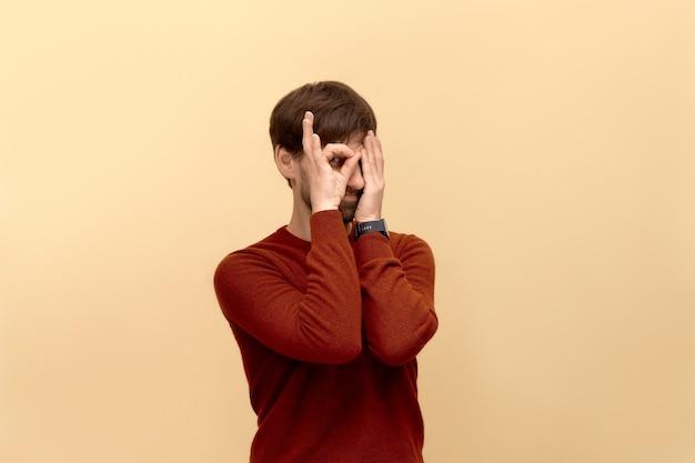 여기 임, 괜찮아. 스웨터를 입고 수염을 가진 재미있는 젊은 남자의 사진, 베이지 색 벽에 포즈를 취하는 손바닥으로 또 다른 절반 얼굴을 덮은 눈 위에 괜찮아 제스처를 확인합니다.