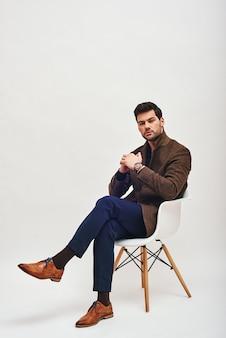 Я слушаю тебя, стильный темноволосый мужчина, сидящий на стуле и смотрящий в камеру