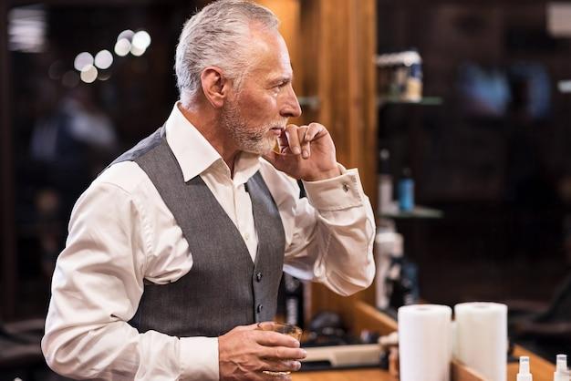 私は最高だ。ブランデーガラスで鏡の前に立っているハンサムな年配の男性。