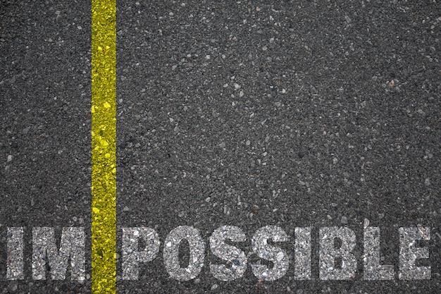 Дорожная разметка желтой краской, разделяющая линию между im и возможным как слово невозможно, концептуальное изображение