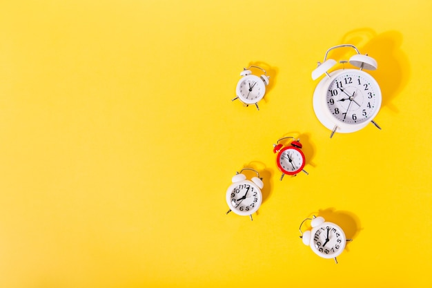 Image of 4 and 1 red alarm clocks on isolated orange wall,