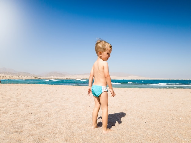 Image of adorable 3 years old little boy walking on the hot beach sand to the sea. child relaxing and having good time during summer holiday vacation.