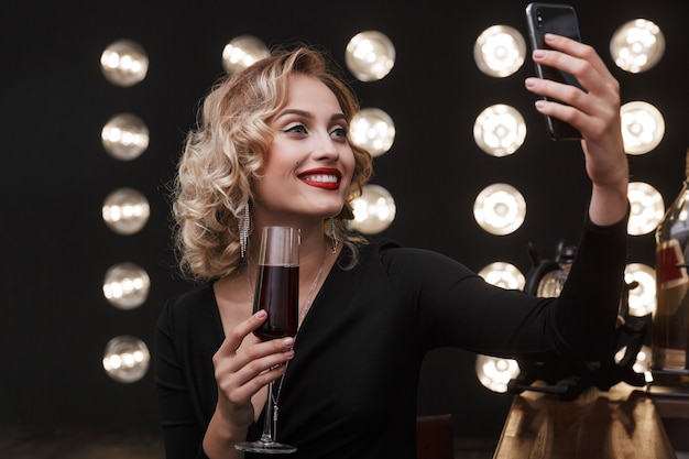 Image of adorable blonde woman wearing elegant dress using cellphone and drinking red wine in bar