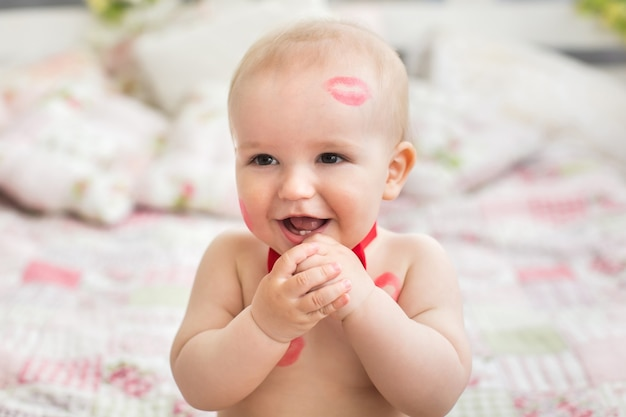 Image of adorable child with red kisses on the skin, happy boy, sitting in the studio on the bed, angel, romantic holiday, valentine's day.