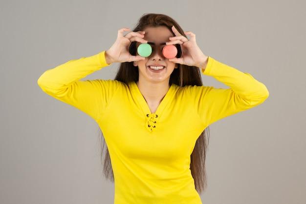 Immagine di una ragazza adorabile in posa con amaretti colorati sul muro grigio.