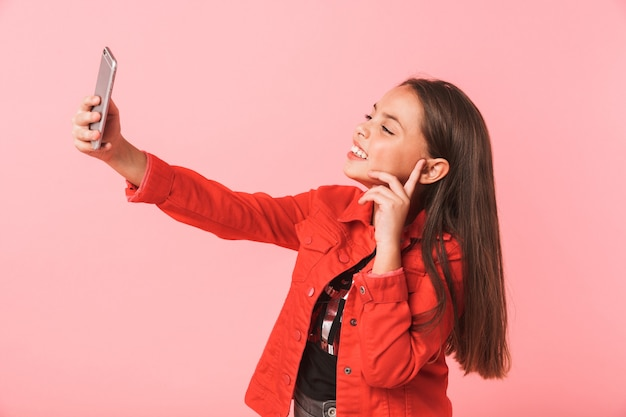 Image of adorable teen girl in casual taking selfie on mobile phone while standing, isolated over red wall