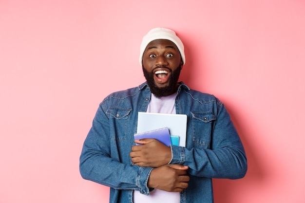 Immagine di un uomo afroamericano adulto che tiene in mano i quaderni e sorride, studia ai corsi, in piedi su sfondo rosa