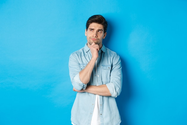 Image of adult bearded man 25s years, thinking about something, looking at upper left corner and pondering ideas, standing over blue background.