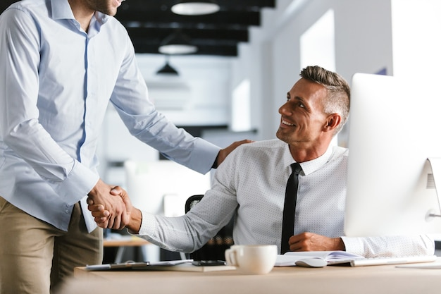 Image of adult businessmen coworkers 30s in formal clothes working in office, and shaking hands together