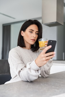 Image of adult woman 30s drinking orange juice and using mobile phone, while resting in bright modern room
