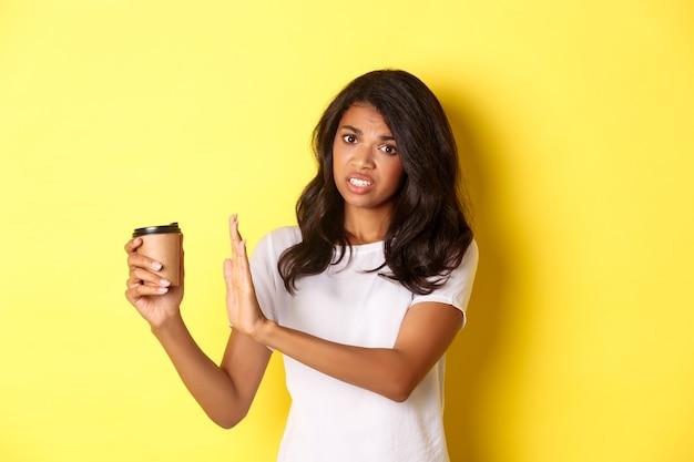 Immagine di una ragazza afro-americana che si lamenta del cattivo gusto del caffè, mostrando il segno di rifiuto e tirando via la tazza, in piedi su sfondo giallo.