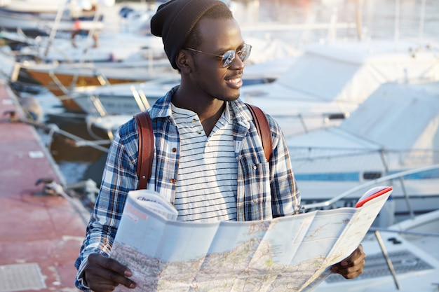Image of african man going for trip, standing in the middle of harbor waiting for his friends, holding paper map, looking excited and cheerful, anticipating new good impressions and experience