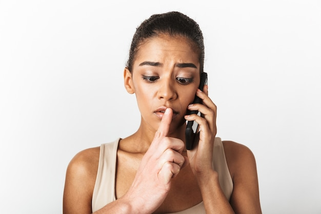 Image of african woman posing talking by mobile phone while someone's hand showing silence gesture.