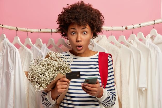 Immagine della donna afroamericana guarda con shock, pone in spogliatoio con vestiti bianchi sui ganci nell'armadio di casa o nel centro commerciale