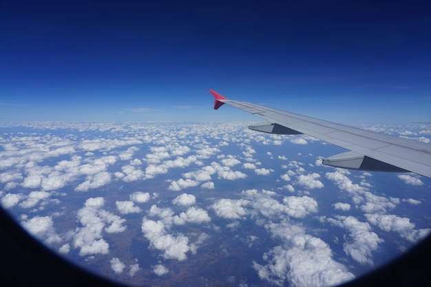 Image of airplane wing and  clouds from the window of plane