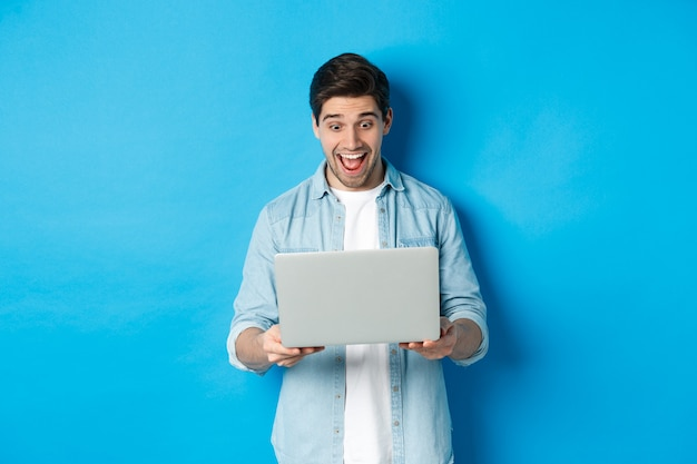Image of amazed and happy man reacting to special offer in internet, looking at laptop excited, standing against blue background.