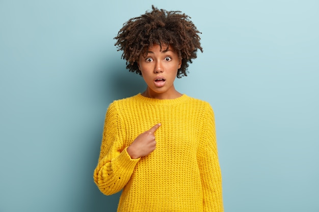 Image of amazed indignant surprised young lady has curly afro hairstyle, being speechless, points at herself, wears yellow sweater