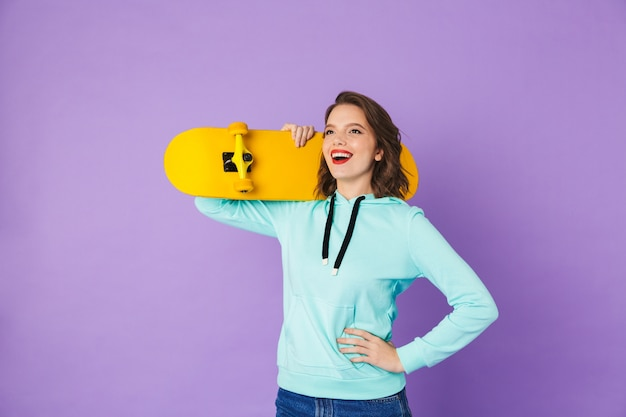 Image of an amazing happy young woman posing isolated over purple wall wall holding skateboard.