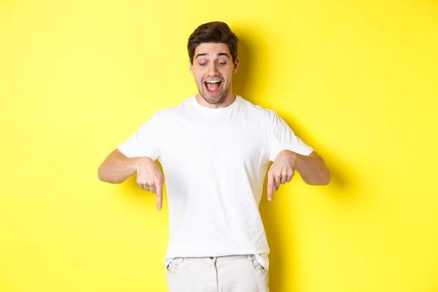 Immagine di un bel ragazzo divertito in maglietta bianca, guardando e puntando le dita verso il basso, in piedi su sfondo giallo.