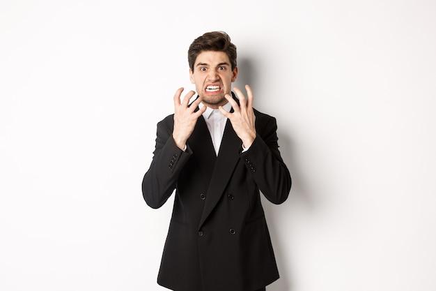 Immagine di uomo d'affari arrabbiato in tuta, guardando con espressione furiosa e pugni serrati, esprimere odio, in piedi matto su sfondo bianco