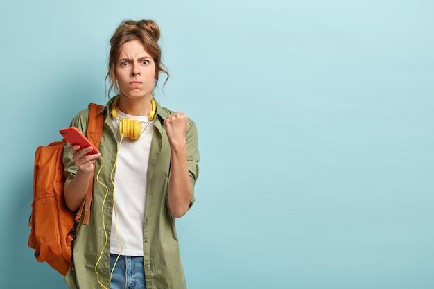 L'immagine della donna millenaria arrabbiata stringe i pugni e guarda con irritazione alla macchina fotografica
