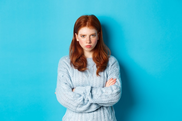 Image of angry redhead girl feeling offended, cross arms on chest and sulking, staring at camera mad, standing against blue background.
