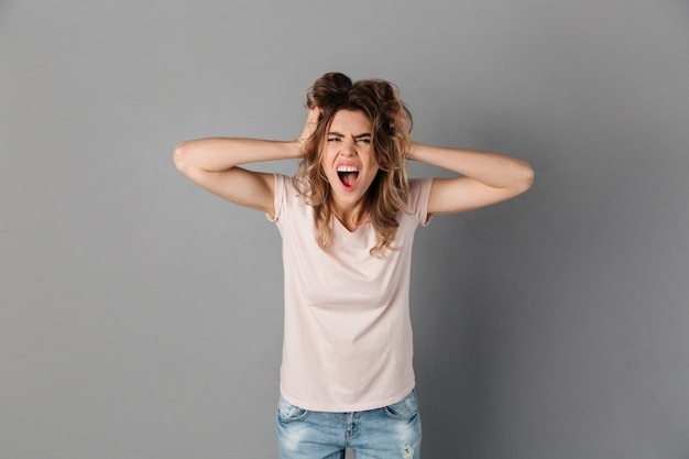Image of angry woman in t-shirt screaming and holding her head over grey