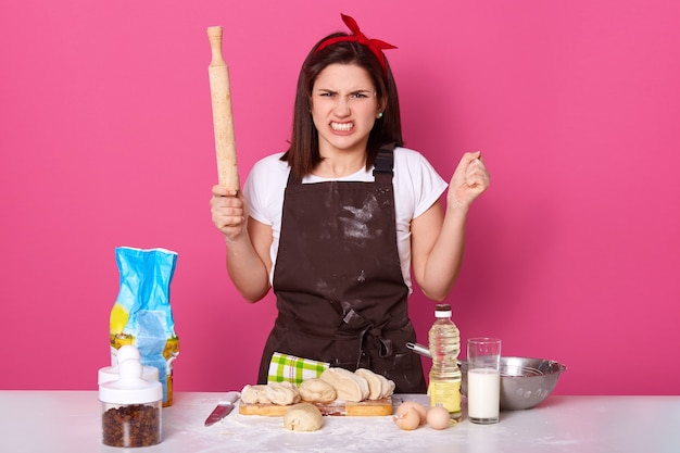 Image of annoyed angry housewife wearing dirty brown apron
