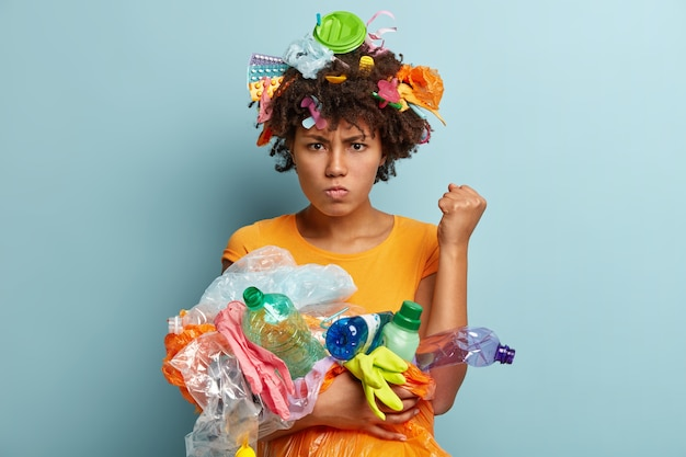 Image of annoyed black woman raises clenched fist, demands to be environmentally friendly, has grumpy facial exrpression, carries plastic waste, uses objects for recycling, stands over blue wall
