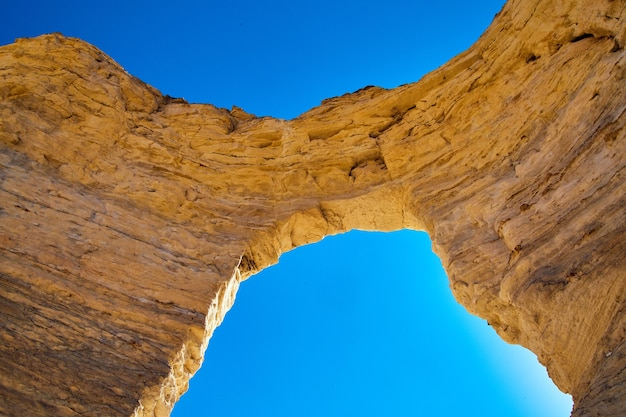 Image of archway of natural white stone against blue sky