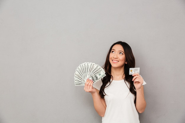 Image of asian content woman 20s holding fan of money dollar banknotes and credit card and looking on copyspace, isolated over gray wall Premium Photo