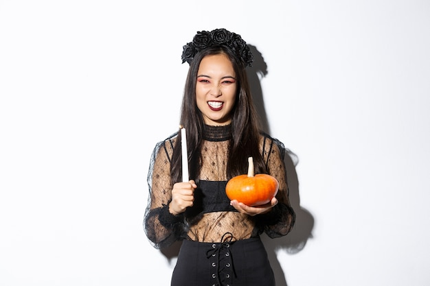 Immagine della strega cattiva asiatica in abito di pizzo gotico e corona nera, ridendo e facendo smorfie, tenendo la candela con la zucca, celebrando halloween
