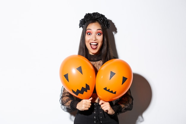 Image of asian girl in evil witch costume holding two orange balloons with scary faces, celebrating halloween, standing over white background.