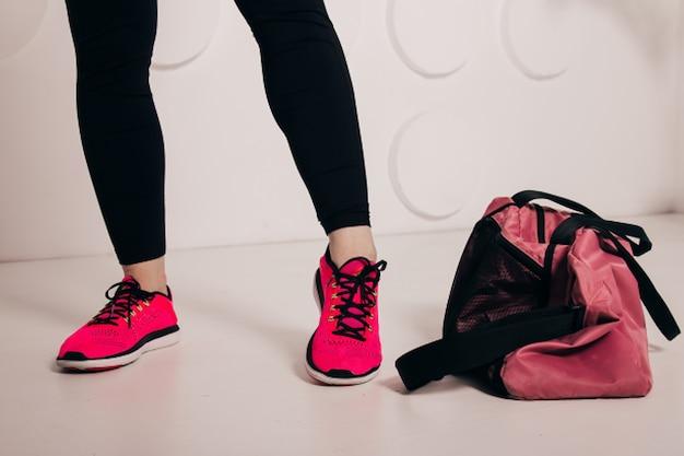 Изображение спереди женской ноги, одетой в черные леггинсы и спортивную обувь, позирующую в студии