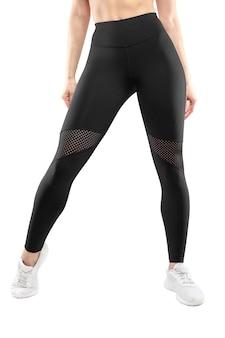 黒のレギンスと白いスポーツシューズを着て、スタジオでポーズをとって、孤立した白い背景の女性の足の前の画像。垂直方向のビュー。