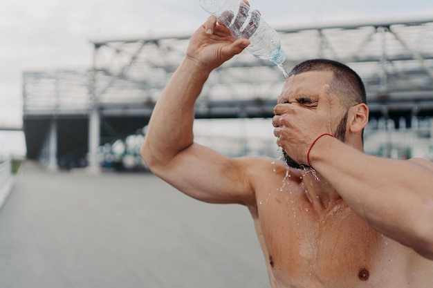 Image of athletic guy with muscular body pours water on himself from bottle, recovers after hard workout, feels tired and thirsty, cools body with cold liquid, loves sport. healthy lifestyle