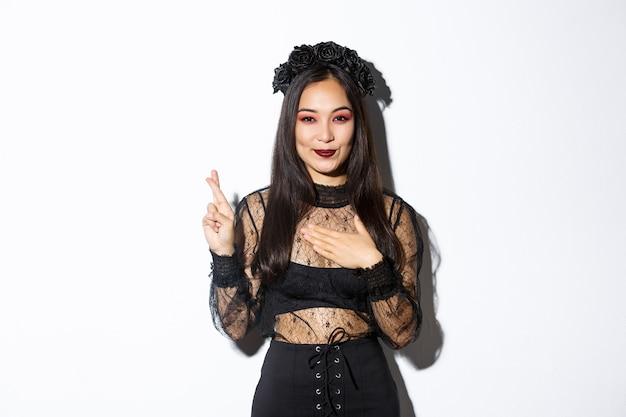 Immagine di donna asiatica attraente in abito da festa di halloween che esprime desiderio, tenendo la mano sul cuore e incrociare le dita per buona fortuna, in piedi su sfondo bianco.