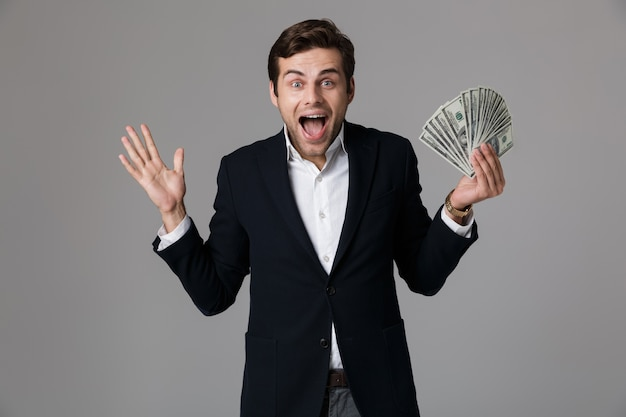 Image of attractive businessman 30s in suit smiling and holding fan of money in dollar banknotes, isolated over gray wall