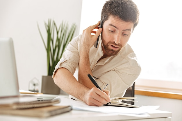 Image of attractive businessman 30s wearing white shirt talking on mobile phone, while sitting at table in modern office