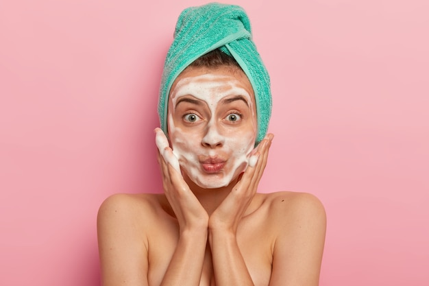Image of attractive female washes face with foam, massages cheeks, looks surprisingly at herself, wears wrapped towel on head, removes dirt, feels freshness after taking shower, models indoor