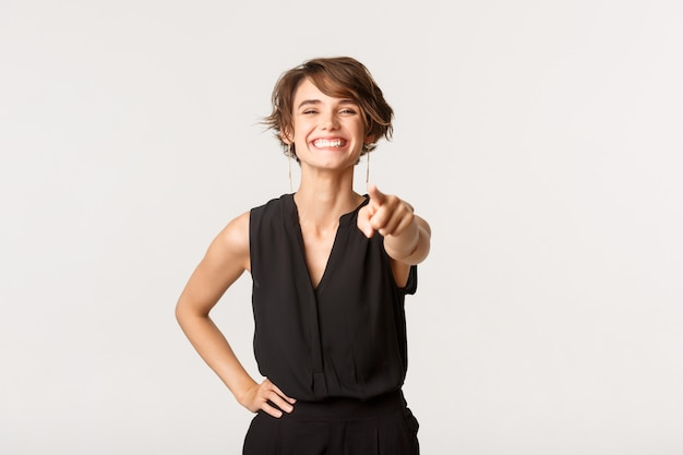 Image of attractive happy woman smiling, pointing finger at you