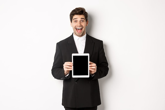 Image of attractive male entrepreneur in trendy suit, showing digital tablet screen and smiling amazed, standing over white background.