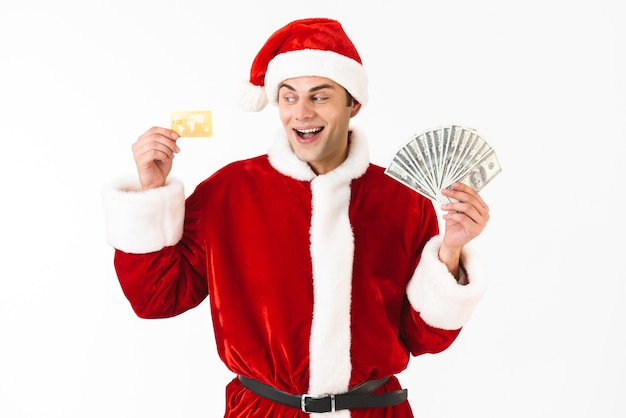 Image of attractive man 30s in santa claus costume holding dollar bills and credit card