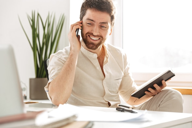 Image of attractive office worker 30s wearing white shirt using smartphone and notebook, while sitting at table in modern workplace