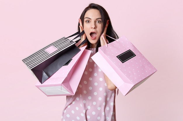 Image of attractive shocked woman, carries shopping bags