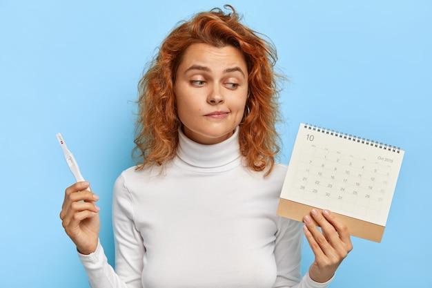 L'immagine della donna attraente tiene il test di gravidanza e il calendario dei periodi