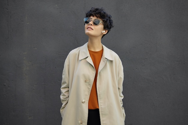 Image of attractive young brunette woman with short curly hair looking upwards with calm face, wearing trendy outfit and sunglasses, standing over city environment