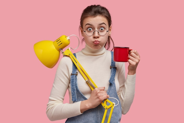 Image of attractive young girl blows cheeks, makes grimace , drinks coffee or tea, uses desk lamp for good light in room, wears round spectacles