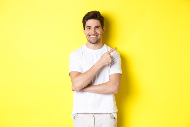 Image of attractive young man pointing finger right at copy space, showing banner or promo offer, standing over yellow background.