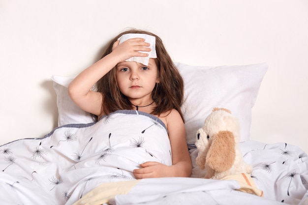 Image of bad looking child holding cold wet napkin on forehead in order to reduce fever